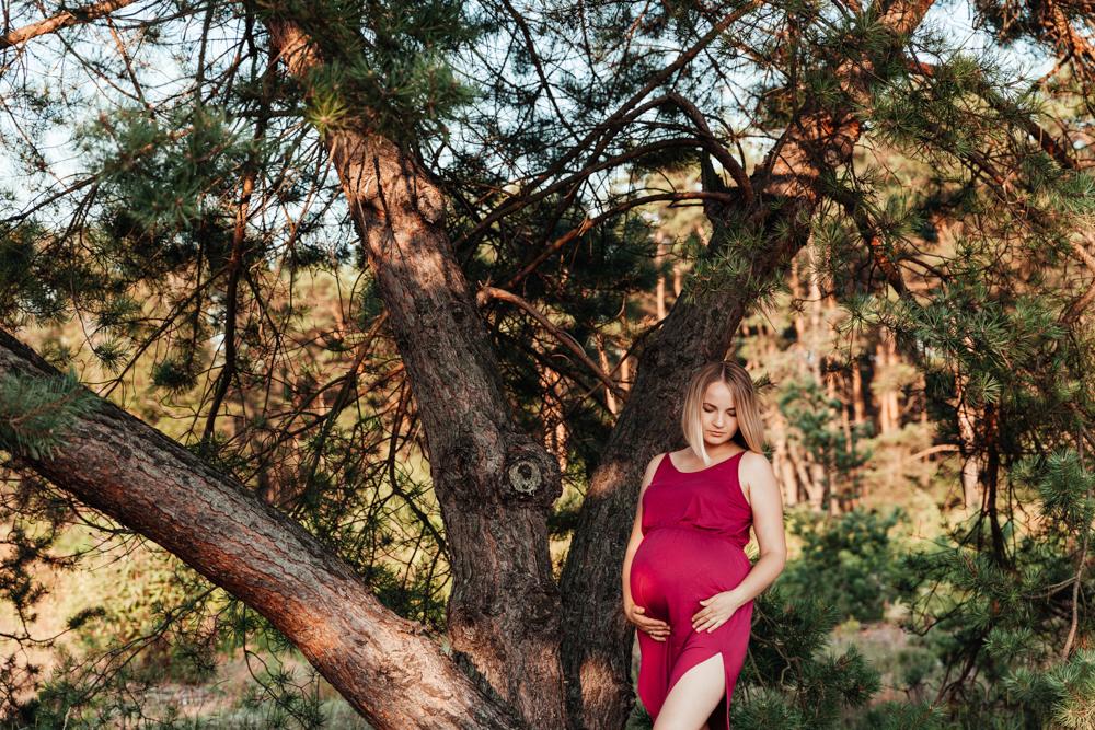 sesja ciązowa w lesie kobieta w czerwonej sukience